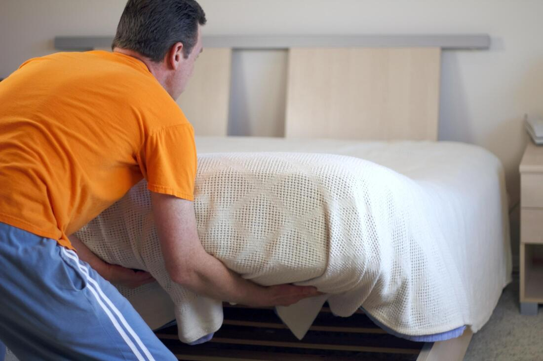 man changing mattress of bed